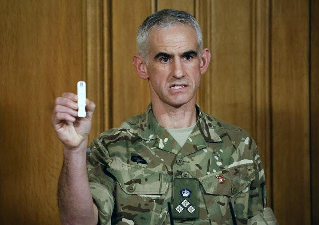 British Army Brigadier Joe Fossey, who is coordinating the mass coronavirus testing pilot in Liverpool, holds up the components of a lateral flow Covid-19 test (Tolga Akmen/PA)