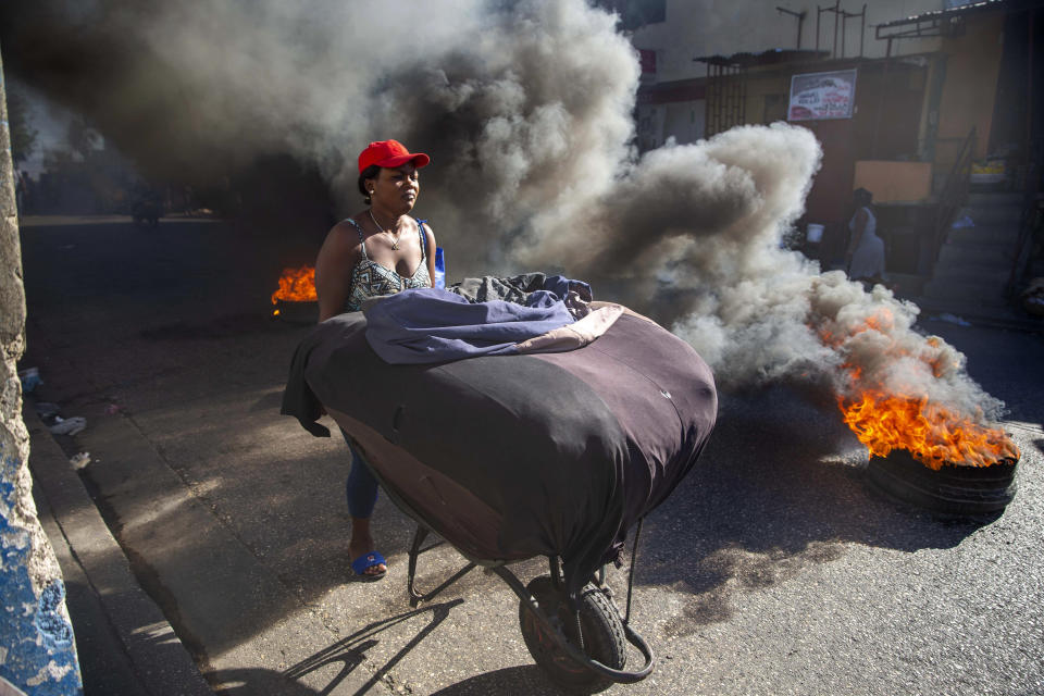 A woman pushes her merchandise away from tires set on fire by protesters during a countrywide strike demanding the resignation of Haitian President Jovenel Moise in Port-au-Prince, Haiti, Monday, Feb. 1, 2021. Opposition leaders are pushing for Moïse to step down on Feb. 7 while he has said his term ends in February 2022. (AP Photo/Dieu Nalio Chery)