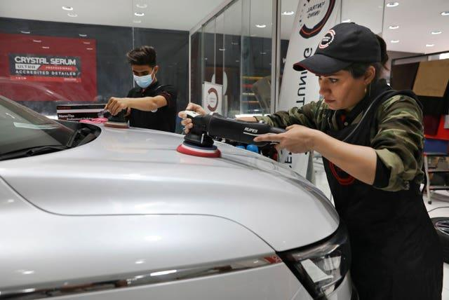 Maryam Roohani, right, and her brother Reza polish a car at a detailing shop in Tehran, Iran
