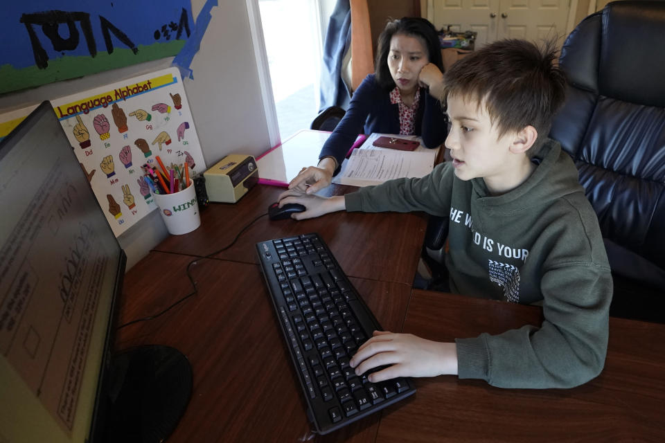 Kim Horrigan, left, sits with her son Conor Horrigan, 8, both of Quincy, Mass., as Conor does math homework at their home, in Quincy, Tuesday, April 13, 2021. Kim said she and her husband have struggled all year with their decision to keep their 8-year-old son in remote learning due to the coronavirus pandemic. (AP Photo/Steven Senne)
