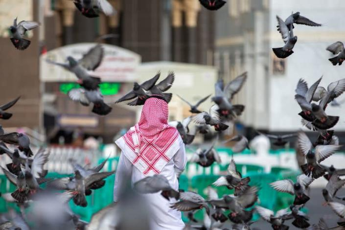 Pigeons are seen flying as a man walks towards the Grand Mosque during the annual Haj pilgrimage, in the holy city of Mecca