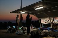 People pray during sunrise as refugees and migrants from the destroyed Moria camp find shelter at the parking space of a supermarket, near a new temporary camp on the island of Lesbos