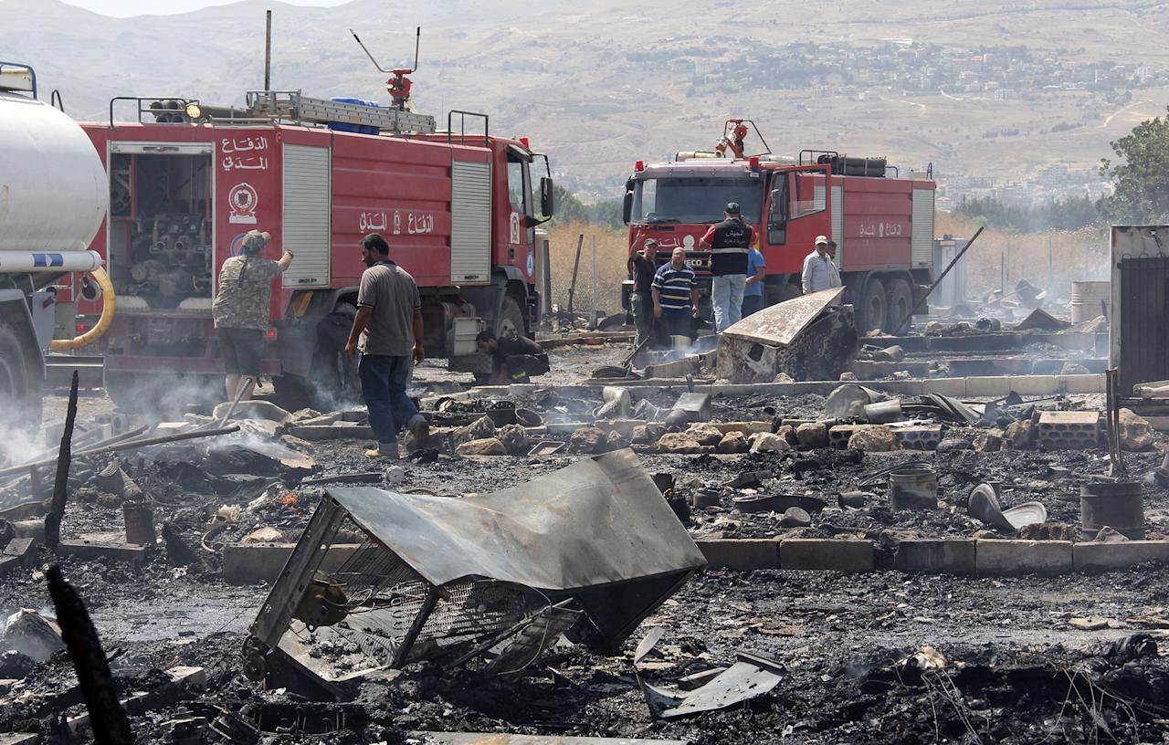 <p>Lebanese firefighters inspect the damage caused by a massive fire in a camp for Syrian refugees near the village of Qab Elias in the Lebanese Bekaa valley on July 2, 2017.<br /> A massive fire in a camp for Syrian refugees in central Lebanon killed one person and wounded six others, the Red Cross said, adding that hundreds were evacuated. (Hassan Jarrah/AFP/Getty Images) </p>