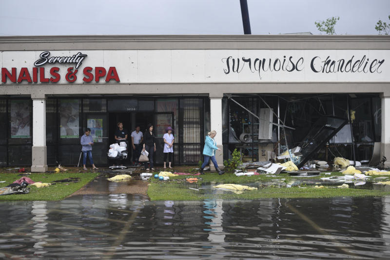 Shop owners and workers stand outside of their shops and walk amongst debris in the Pemberton Quarters strip mall following severe weather Saturday, April 13, 2019 in Vicksburg, Miss. Authorities say a possible tornado has touched down in western Mississippi, causing damage to several businesses and vehicles. John Moore, a forecaster with the National Weather Service in Jackson, says a twister was reported Saturday in the Vicksburg area of Mississippi and was indicated on radar. (Courtland Wells/The Vicksburg Post via AP)