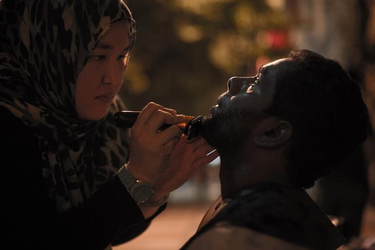 Azmina Burhan, who runs a salon but volunteers with the Pertiwi Sou Kitchen, trims the beard of a homeless man in downtown Kuala Lumpur, on November 13, 2013