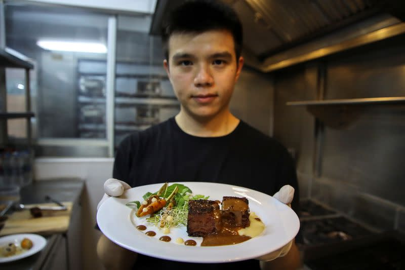 Thai inventor Sorawut Kittibanthorn presents a steak dish made from chicken feathers at a kitchen in Bangkok