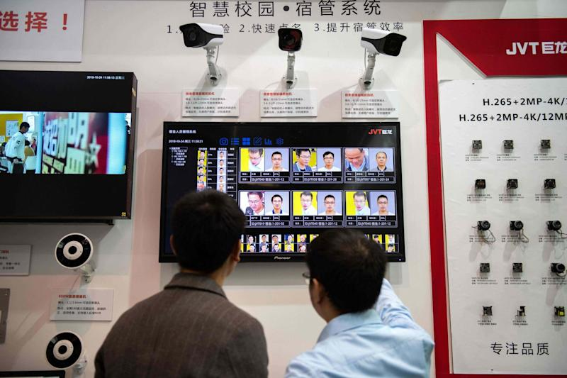 Visitors looking at AI (artificial intelligence) security cameras with facial recognition technology at the China International Exhibition Center in Beijing in 2018: AFP via Getty Images