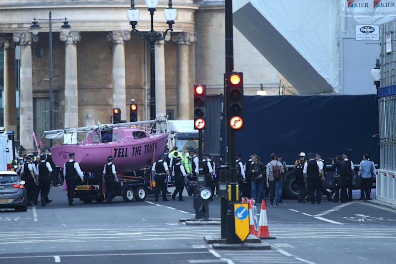 Police follow a lorry towing away the XR movement's pink boat (PA)
