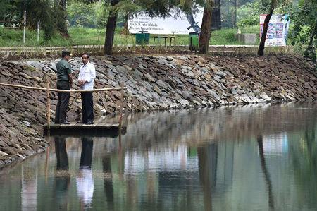 Indonesia President Joko Widodo (R) talks with the local military commander during a visit to Lake Cisanti, the source of the Citarum River, south of Bandung, West Java