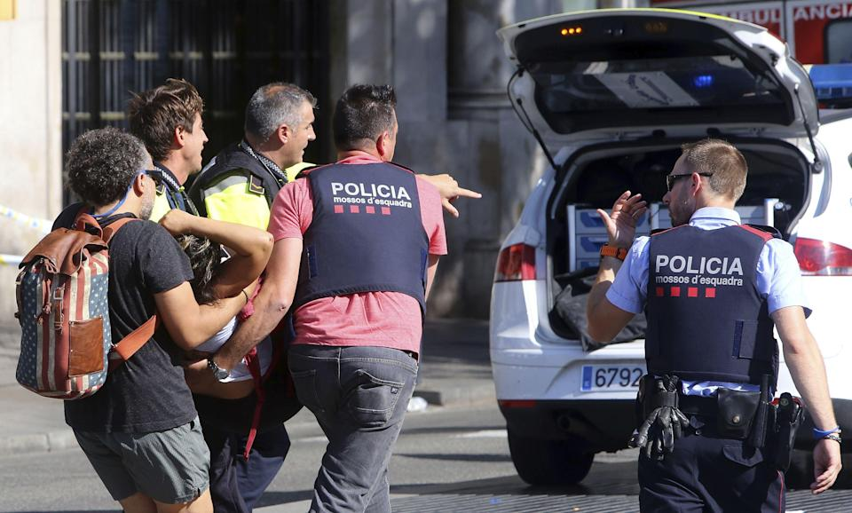 Officers help one of the victims of the Barcelona attack (Rex)