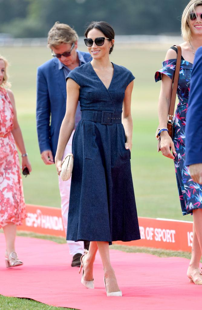 Meghan Markle wears a Carolina Herrera belted denim midi dress, Tom Ford sunglasses, J.Crew clutch, and Aquazzura heels at Royal County of Berkshire Polo Club on July 26, 2018. (