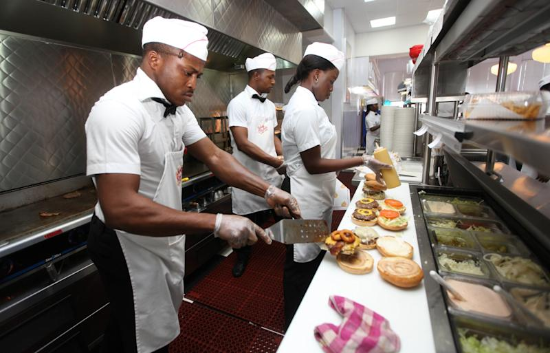 In this photo taken, Wednesday, Jan. 23, 2013 workers prepare hamburgers   at Johnny Rockets restaurant in Lagos, Nigeria. As Nigeria's middle class grows along with the appetite for foreign brands in Africa's most populous nation, more foreign restaurants and lifestyle companies are entering the country. And the draw on Nigerians' new discretionary spending has also put new expectations on providing quality service in a nation where many have grown accustomed to expecting very little. ( AP Photo/Sunday Alamba)