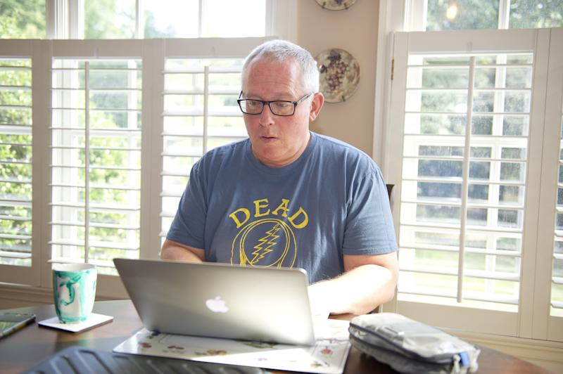 Michael Caputo sits while working on a laptop wearing a Grateful Dead T-shirt