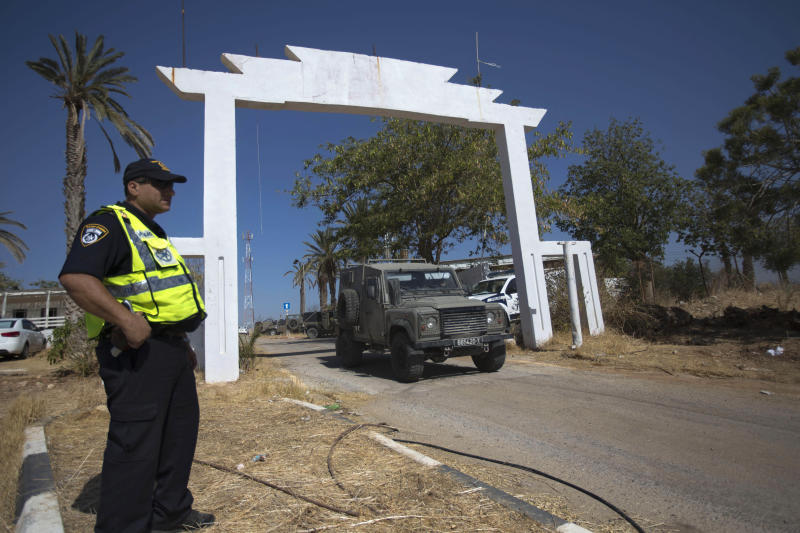 An Israeli policeman stands at the entrance to the site where an Israeli man was killed in the northern Jordan Valley, Friday, Oct. 11, 2013. Palestinians wielding axes and iron bars killed an Israeli man outside his home in the West Bank, the Israeli police said Friday, the latest in a series of attacks on Israelis in the area. (AP Photo/Sebastian Scheiner)