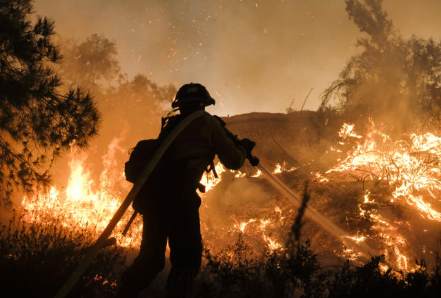 <p>A firefighter battles the Holy Fire burning in the Cleveland National Forest along a hillside at Temescal Valley in Corona, Calif., Thursday, Aug. 9, 2018. (Photo: Ringo H.W. Chiu/AP) </p>
