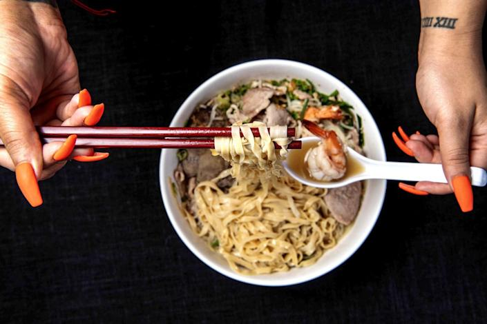Hands hold chopsticks with noodles and a spoonful of shrimp above a bowl of House Special Noodles.