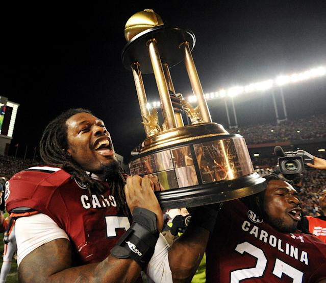 South Carolina defensive end Jadeveon Clowney (7) and South Carolina cornerback Victor Hampton (27) hold the Hardee's Trophy after defeating Clemson 31-17 in an NCAA college football game on Saturday, Nov. 30, 2013, in Columbia, S.C. (AP Photo/Rainier Ehrhardt)