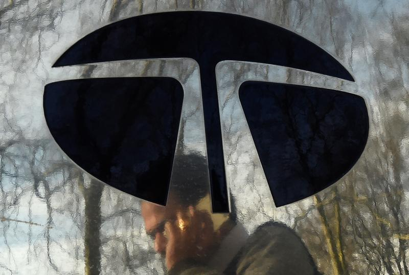 A man walks past a Tata sign outside their offices in London