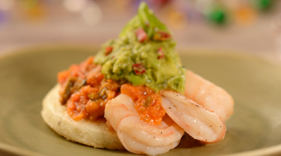 Arepa topped with Shrimp, Crushed Avocado Aji and Tomato Sauce. (Disney)