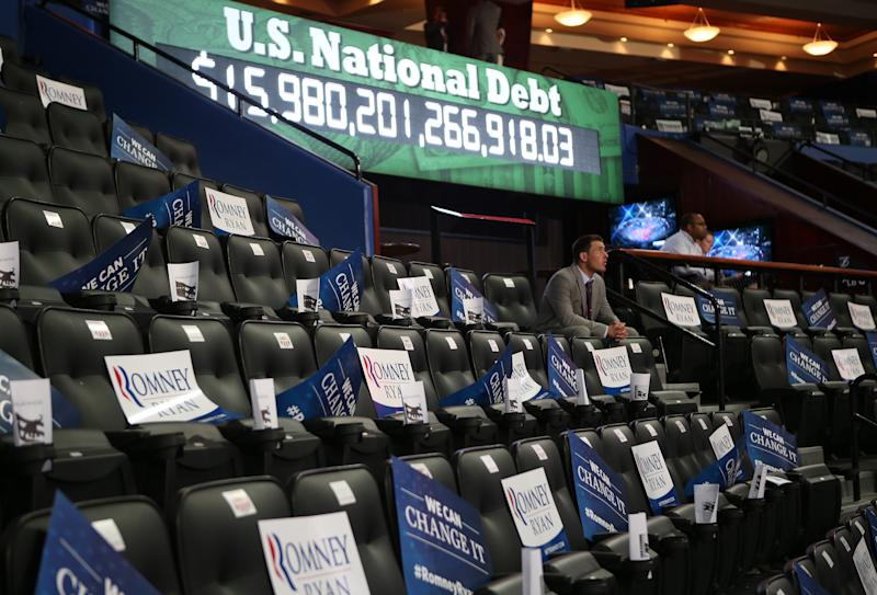 TAMPA, FL - AUGUST 29: A man sits among campaign signs in front of a U.S. national debt clock during the third day of the Republican National Convention at the Tampa Bay Times Forum on August 29, 2012 in Tampa, Florida. Former Massachusetts Gov. Former Massachusetts Gov. Mitt Romney was nominated as the Republican presidential candidate during the RNC, which is scheduled to conclude August 30. (Photo by Chip Somodevilla/Getty Images)