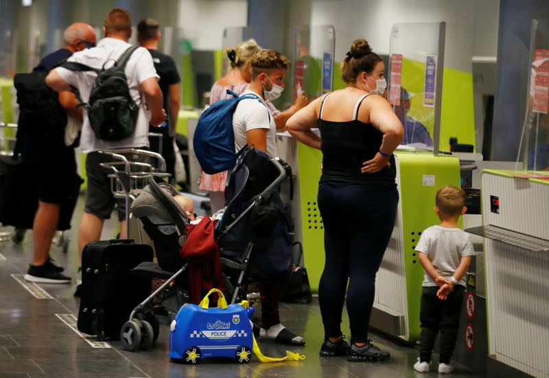British tourists returning to UK, check in their luggage, as Britain imposed a two-week quarantine on all travellers arriving from Spain