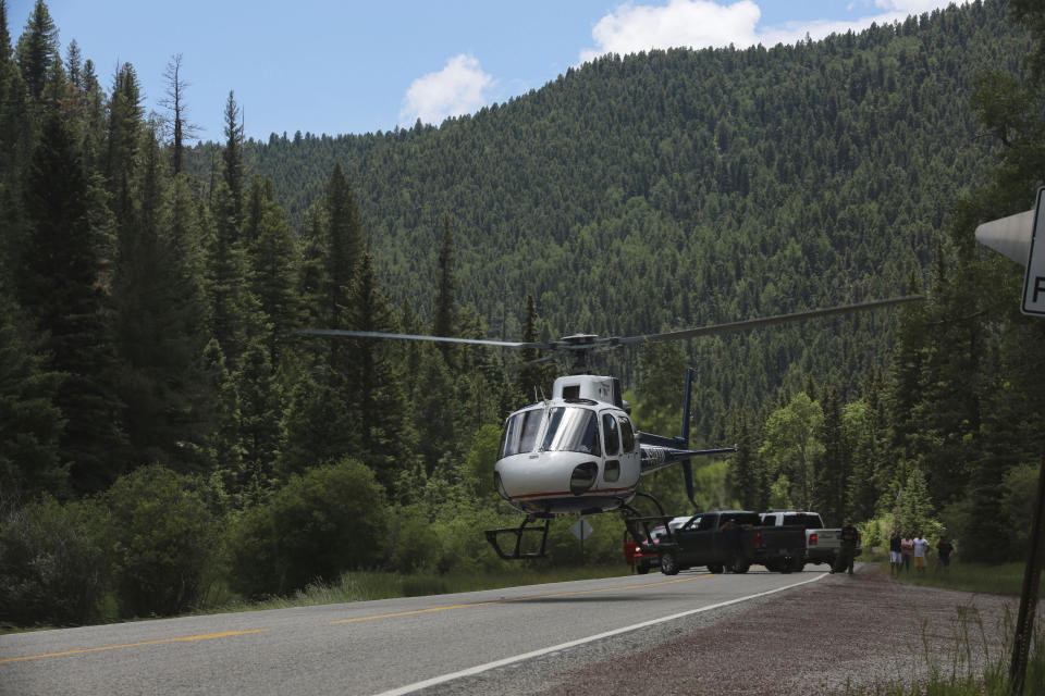 Medical staff lift off carrying an elderly patient from a remote highway on Friday, July 2, 2021, in the Carson National Forest, outside of Taos, N.M. The man fell ill at a remote encampment as part of the annual Rainbow Gathering. More than 2,000 people have made the trek into the mountains of northern New Mexico as part of an annual counterculture gathering of the so-called Rainbow Family. While past congregations on national forest lands elsewhere have drawn as many as 20,000 people, this year's festival appears to be more reserved. Members (AP Photo/Cedar Attanasio)