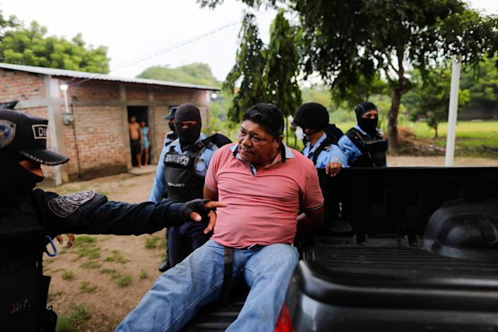 Honduran police officers detain a man on suspicion for his role in killing Giorgio Scanu, 65, who was lynched by a mob of more than 600 villagers in revenge for allegedly murdering a homeless man (REUTERS)