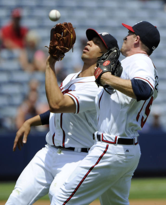 Atlanta Braves shortstop Andrelton Simmons, left, fields the infield pop fly by San Diego Padres' Yonder Alonso for the out as second baseman Phil Gosselin (15) backs Simmons up during the second inning of a baseball game Monday, July 28, 2014, in Atlanta. (AP Photo/David Tulis)