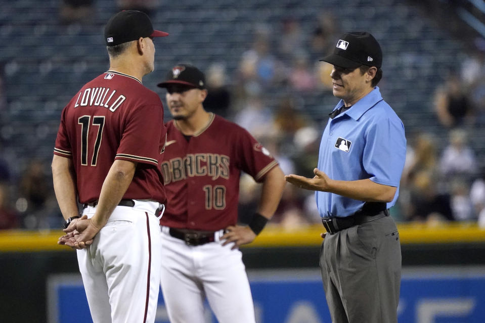 Arizona Diamondbacks manager Torey Lovullo (17) discuses a call with umpire D.J. Reyburn during the fifth inning of a baseball game against the Milwaukee Brewers, Wednesday, June 23, 2021, in Phoenix. (AP Photo/Matt York)