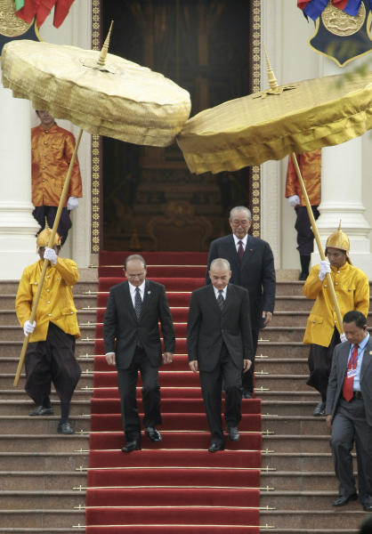 Cambodian King Norodom Sihamoni, front center right, accompanies Myanmar President Thein Sein, center left, as they walk on the red carpet after a welcome meeting at the Cambodian Royal Palace in Phnom Penh, Cambodia, Wednesday, March 21, 2012. (AP Photo/Heng Sinith)