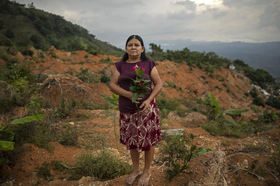 """Olga Ondina, 52, stands for a portrait at the site of her home which was destroyed by a landslide triggered by hurricanes Eta and Iota in the village of La Reina, Honduras, Wednesday, June 23, 2021. """"I love flowers, and now I take a bouquet with me where I now live in a rented house. Everything that happened to us is very sad, my parents lived and died here, my children were born here. Today I came to cry,"""" she said. (AP Photo/Rodrigo Abd)"""