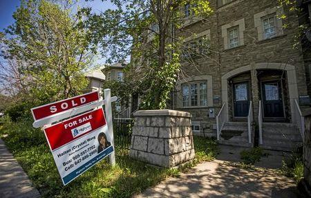 FILE PHOTO: A sign stands in front of a home that has been sold in Toronto