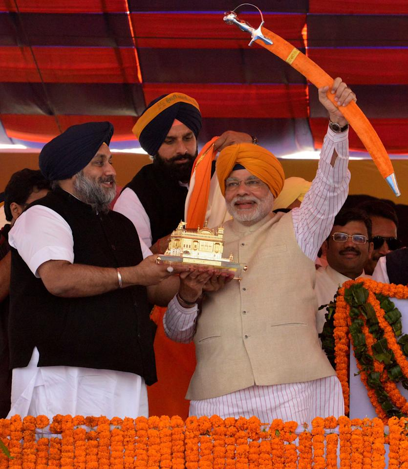 Hindu nationalist Narendra Modi (R), prime ministerial candidate for India's main opposition Bharatiya Janata Party (BJP) and Gujarat's chief minister, is presented with a sword and a memento by Punjab deputy Chief Minister Sukhbir Singh Badal during a rally at Jagraon in Ludhiana, in the northern Indian state of Punjab, February 23, 2014. Opposition leader Modi has widened his lead as candidate to become India's prime minister and his Hindu nationalist BJP is likely to emerge as the single largest party in coming elections, according to the ABP News-Nielsen poll forecast, published on Saturday. REUTERS/Stringer (INDIA - Tags: POLITICS ELECTIONS)