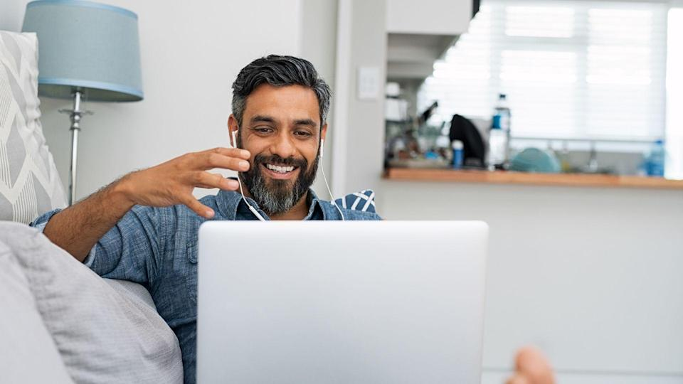 Happy mature man relaxing on couch while video calling using laptop at home.