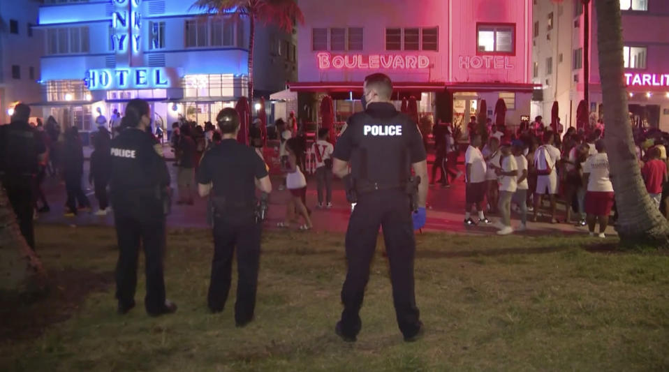 In this image taken from video, police officers stand guard Saturday evening, March 20, 2021, as crowds descend on South Beach in Miami. After days of partying and confrontations between police and large crowds, Miami Beach officials have ordered an emergency curfew. (WPLG via AP)