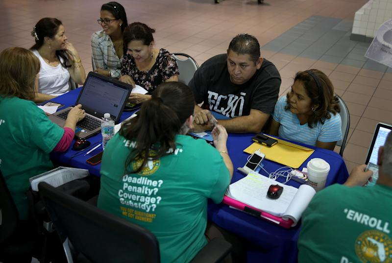 MIAMI, FL - DECEMBER 22: Rene Hernandez (2nd R) and his wife Nery Hernandez speak with Rosaly Hernandez an insurance agent with Sunshine Life and Health Advisors as they try to purchase health insurance under the Affordable Care Act at the kiosk setup at the Mall of Americas on December 22, 2013 in Miami, Florida. Tomorrow is the deadline for people to sign up if they want their new health benefits to kick in on the 1st of January. People have until March 31, to sign up for coverage that would start later. (Photo by Joe Raedle/Getty Images)