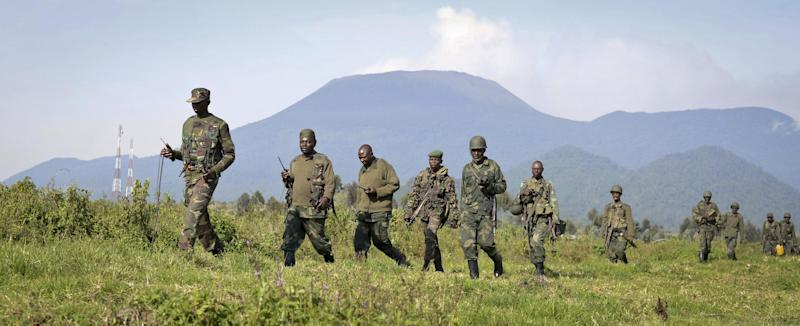 Congolese army soldiers march on a reconnaissance mission near Kibumba Hill, which is occupied by M23 rebels, around 25km from the provincial capital Goma, in eastern Congo Sunday, Oct. 27, 2013. The Congolese army says it has taken two more towns in the North Kivu province of eastern Congo in fresh fighting around Kibumba town using tanks and heavy artillery against the M23 rebels. (AP Photo/Joseph Kay)