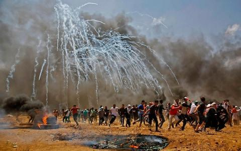 <span>Palestinians run for cover as tear gas rains down near the border between Israel and the Gaza Strip</span> <span>Credit: Mohammed Abed/AFP </span>