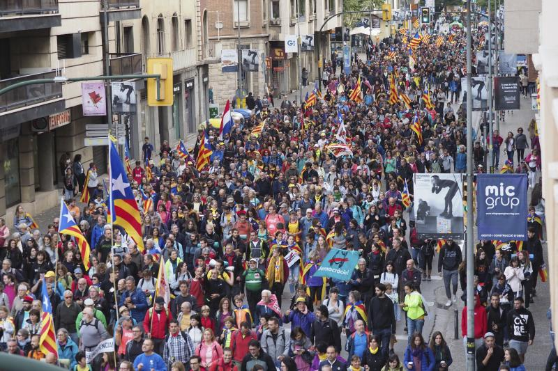 Demonstrators a long a street in Girona, Spain, Wednesday, Oct. 16, 2019. Thousands of people have joined five large protest marches across Catalonia that are set to converge on Barcelona, as the restive region reels from two straight days of violent clashes between police and protesters. The marches set off from several Catalan towns and aimed to reach the Catalan capital by Friday. (AP Photo/Mar Grau)