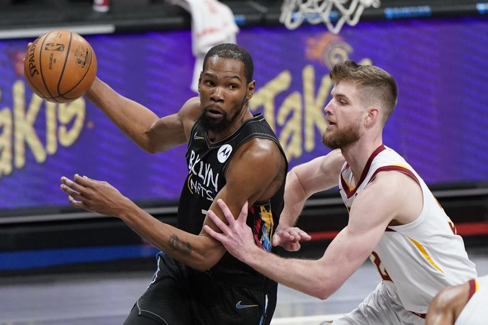 Brooklyn Nets' Kevin Durant, left, drives past Cleveland Cavaliers' Dean Wade during the first half of an NBA basketball game Sunday, May 16, 2021, in New York. (AP Photo/Frank Franklin II)