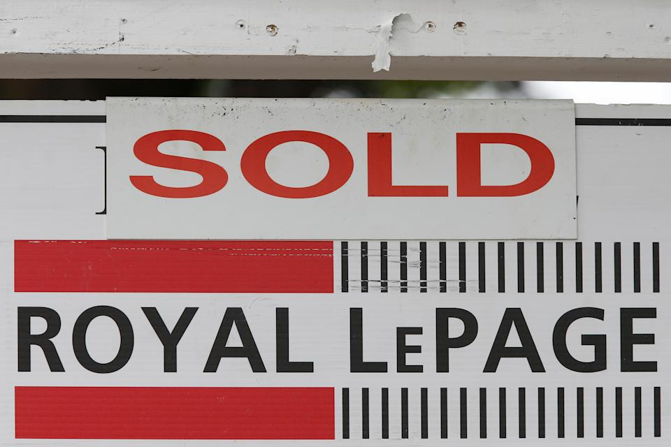 """A Royal LePage real estate sign is marked """"Sold"""" in front of a house in Ottawa, Ontario, Canada, August 15, 2017. REUTERS/Chris Wattie"""