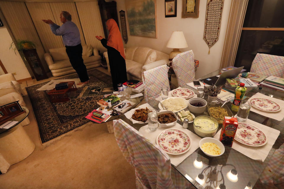 In this Tuesday, April 28, 2020, photo, Asghar Ali Khan and his wife Shaheen, participate in the evening prayer as the Iftar, the evening meal with which Muslims end their daily Ramadan fast at sunset, waits on the dining room table at their Wheeling,Ill., home. (AP Photo/Charles Rex Arbogast)