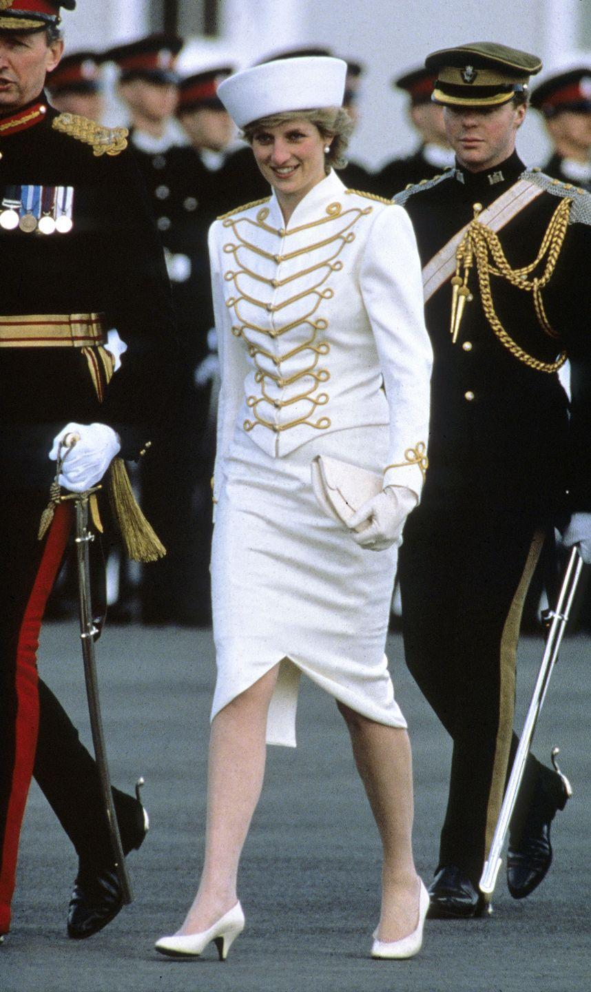 <p>In a white military-inspired dress, hat and heels while visiting the Sandhurst Military Academy in England. </p>