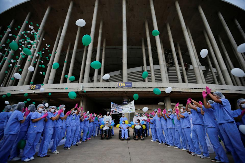 Medical professionals release balloons as last patients leave the temporary field hospital at the Mane Garrincha Stadium, after being treated for the coronavirus disease (COVID-19) and discharged in Brasilia, Brazil, October 15, 2020. REUTERS/Adriano Machado