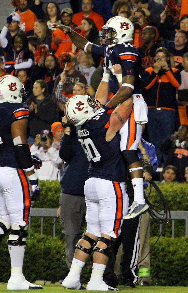 Auburn quarterback Nick Marshall, top, celebrates with Auburn center Reese Dismukes (50) after scoring a touchdown on a quarterback keeper during the first half of an NCAA college football game against Florida Atlantic on Saturday, Oct. 26, 2013, in Auburn, Ala. (AP Photo/Butch Dill)