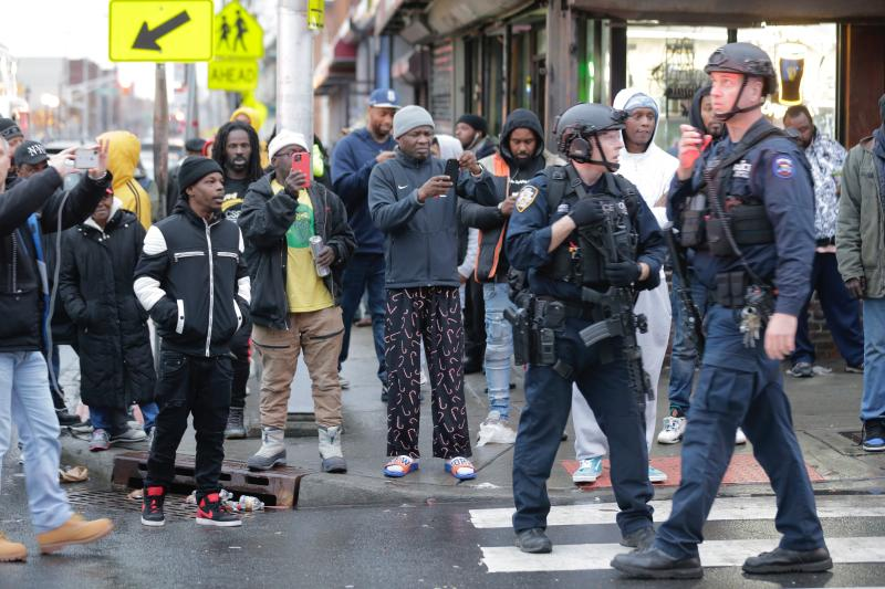 Bystanders look on as law enforcement arrive on the scene following reports of shooting, Tuesday, Dec. 10, 2019, in Jersey City, N.J. (AP Photo/Seth Wenig)