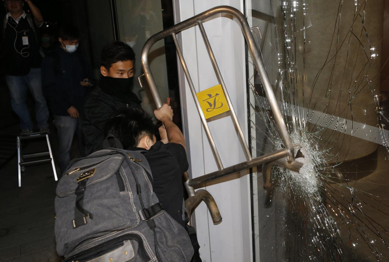 "Masked pro-democracy protesters try to break with a fence a glass window of the Legislative Council in Hong Kong early November 19, 2014, in response to an earlier clear up of part of the ""Occupy Central"" protest site. Hong Kong on Tuesday cleared part of a protest camp in the heart of the city that has been occupied by pro-democracy demonstrators for nearly two months, leaving most of the main protest site intact..  REUTERS/Tyrone Siu  (CHINA - Tags: POLITICS BUSINESS EDUCATION CRIME LAW)"
