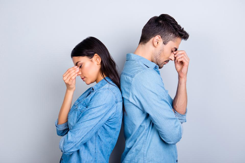 Two entrepreneurs overworked holding their fingers on nose between eyes, relationship of young family came to the dead end, standing over grey background