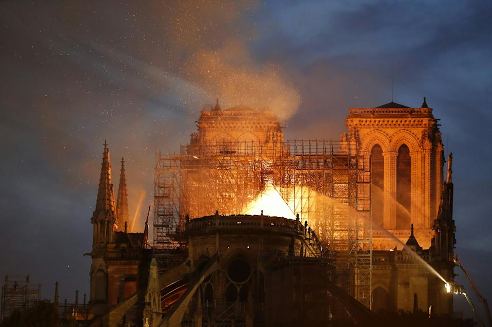Firefighters douse flames billowing from the roof at Notre-Dame Cathedral in Paris on April 15, 2019.