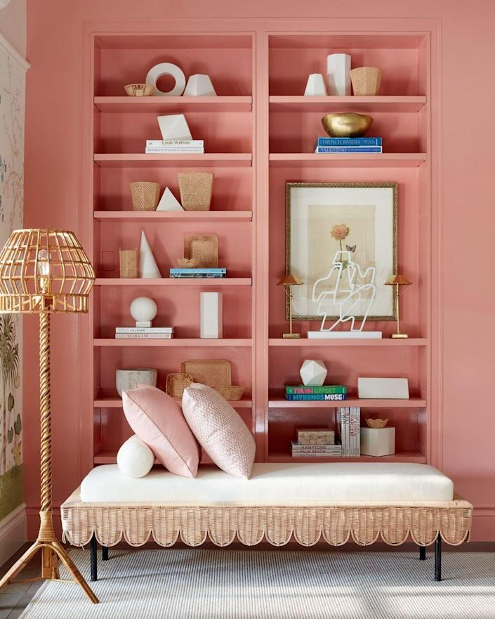 """<p>Juicy watermelon tones anchor the tall bookshelves of this sprawling <a href=""""https://www.veranda.com/decorating-ideas/a30641052/kips-bay-decorator-show-house-palm-beach-2020/"""" rel=""""nofollow noopener"""" target=""""_blank"""" data-ylk=""""slk:Palm Beach living room"""" class=""""link rapid-noclick-resp"""">Palm Beach living room</a> by Atlanta-based designer <a href=""""http://suzannekasler.com/"""" rel=""""nofollow noopener"""" target=""""_blank"""" data-ylk=""""slk:Suzanne Kasler"""" class=""""link rapid-noclick-resp"""">Suzanne Kasler</a>. The carmine-pink (Custis Salmon by <a href=""""https://www.benjaminmoore.com/en-us"""" rel=""""nofollow noopener"""" target=""""_blank"""" data-ylk=""""slk:Benjamin Moore"""" class=""""link rapid-noclick-resp"""">Benjamin Moore</a>) energizes the flora and fauna wallcovering (<a href=""""https://degournay.com/"""" rel=""""nofollow noopener"""" target=""""_blank"""" data-ylk=""""slk:de Gournay"""" class=""""link rapid-noclick-resp"""">de Gournay</a>) and rattan furniture without competing with them. </p>"""